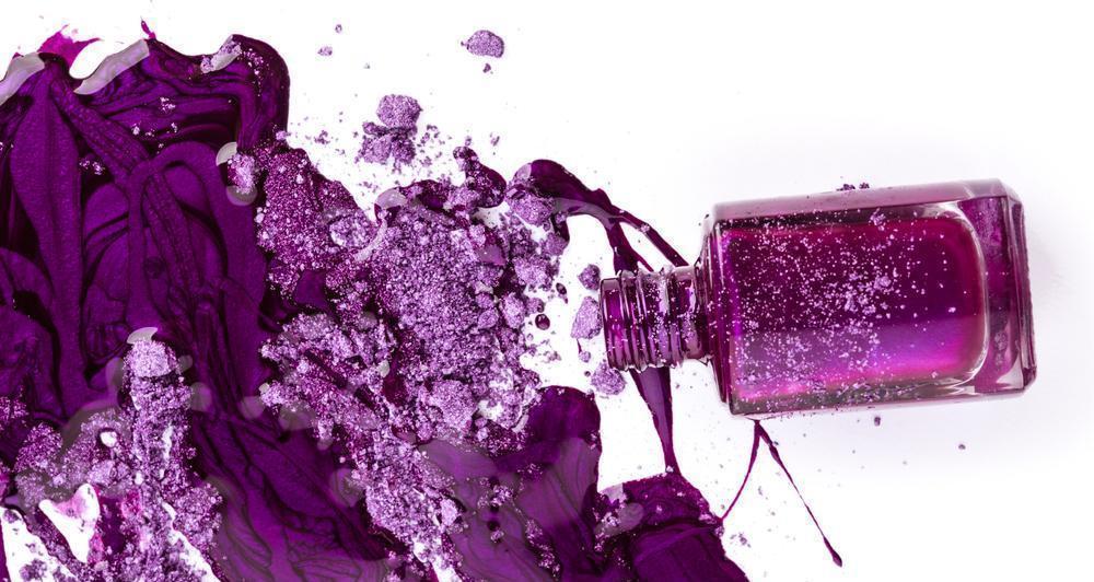 Purple nail polish and crushed eye shadow on white background